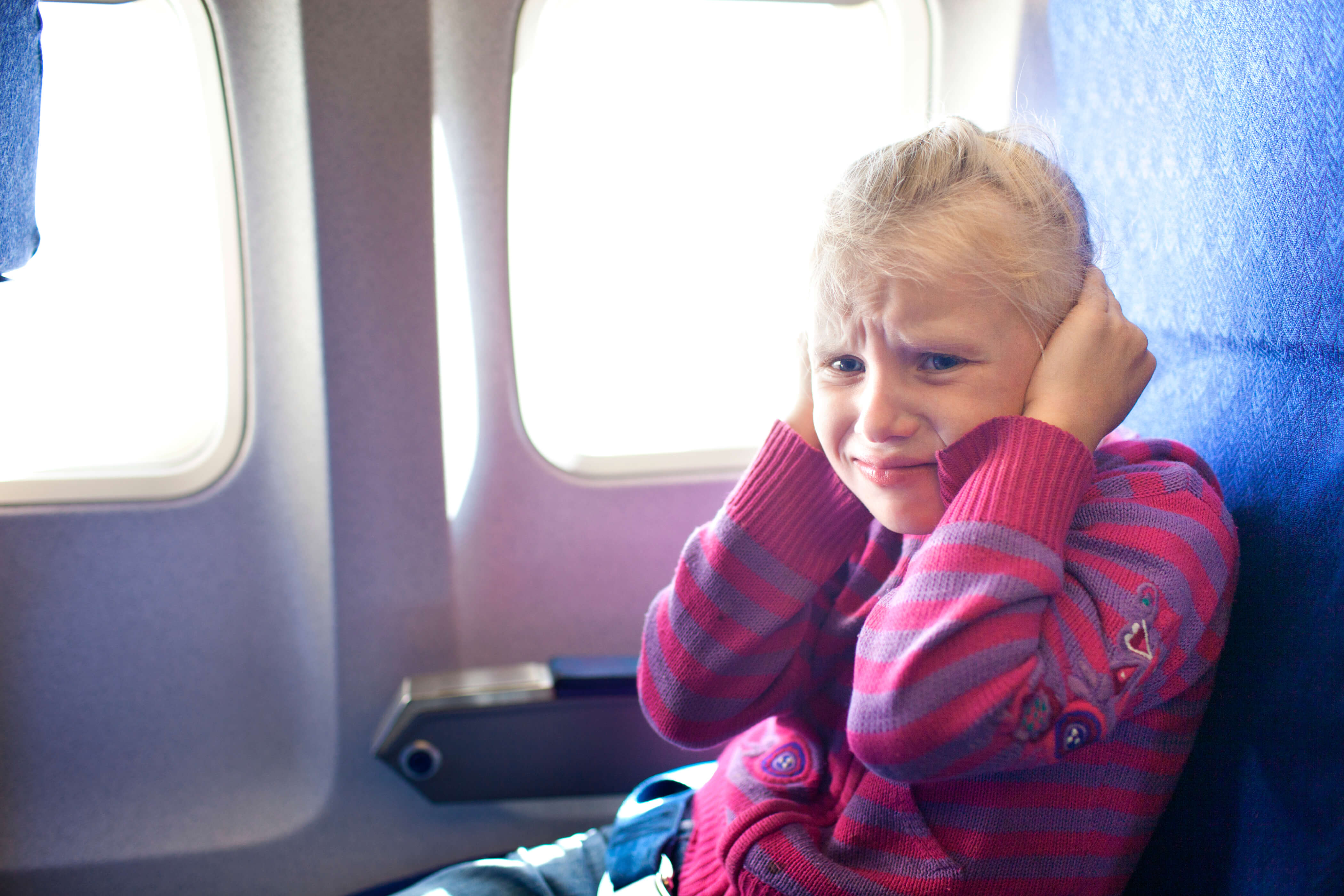 Niña tapándose los oídos en un avión