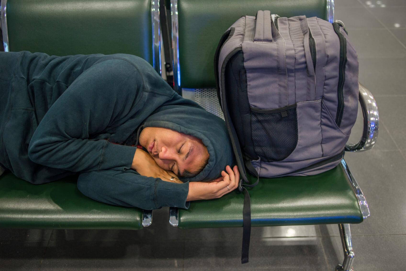 Hombre durmiendo en un aeropuerto