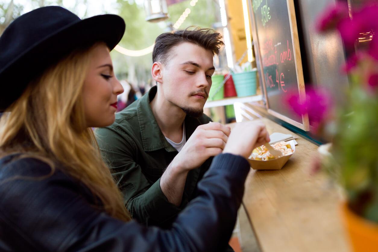 Jóvenes comiendo en un puesto de comida callejera
