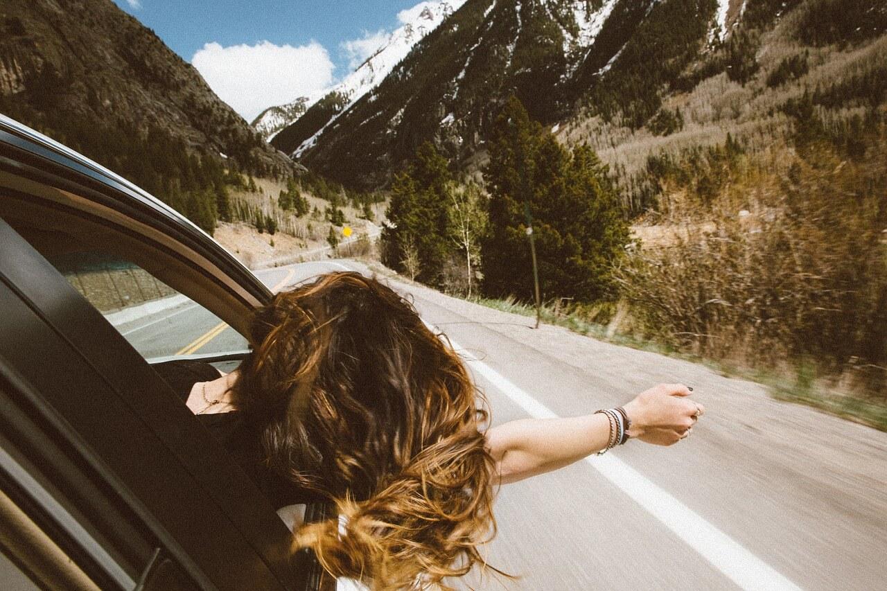 Mujer en un auto por la carretera