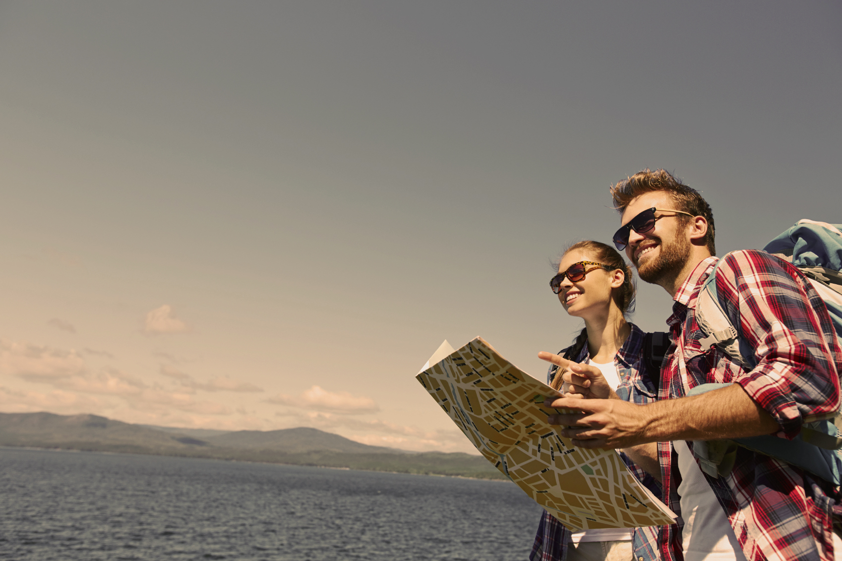 Amorous hikers with map on background of the sea