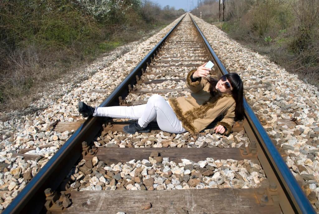 Mujer tomándose una selfie en las líneas del tren