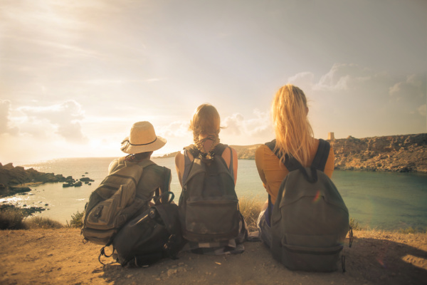 Photo of three girl who are sitting back to the photographer and looking at the beautiful panorama